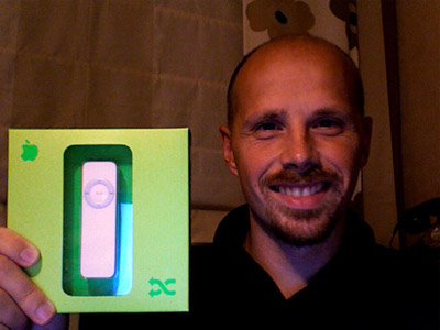A picture of me and an iPod Shuffle in its box.