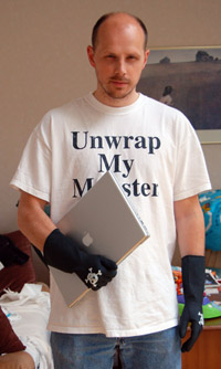 A picture of me holding a MacBook Pro, with plastic gloves with skull and bones on them, and a t-shirt reading: Unwrap My Monster
