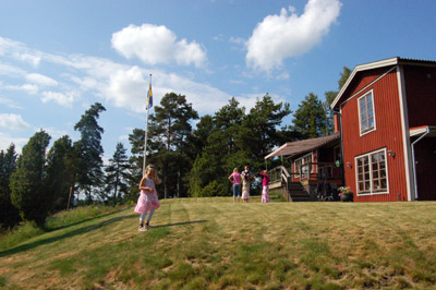 A summer picture with a Swedish flag and a Swedish traditional red wood house